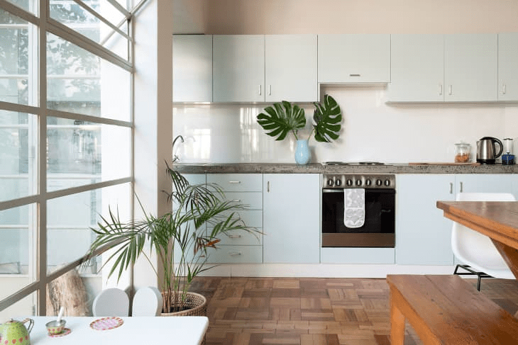an airy contemporary kitchen in light blue, with a concrete countertops and a sleek white glass backsplash plus tropical plants