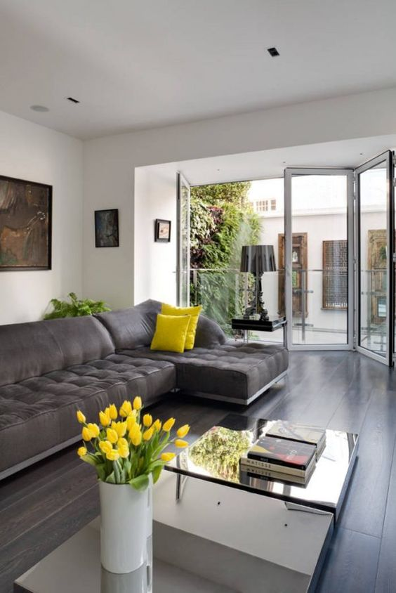 an airy living room with a graphite grey sectional, mirror coffee tables, touches of bold yellow and a glazed wall