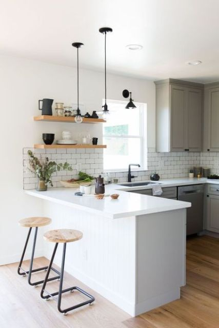 an airy two tone Scandinavian kitchen with a white kitchen island, white subway tiles, black touches for a dramatic look