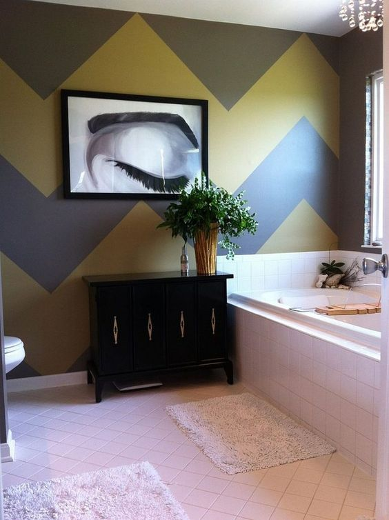 an artistic bathroom with a chevron gray and yellow wall, white tiles, a black cabinet and a chic artwork is wow