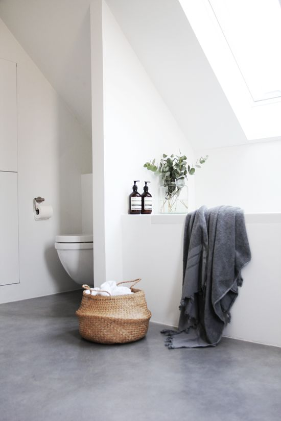 an attic Scandinavian bathroom with white walls, a grey floor, skylights and a tub feels very airy