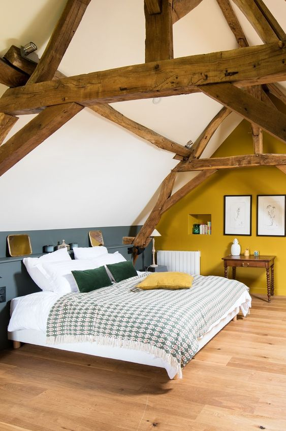 an attic barn bedroom with a mustard accent wall, a grey and white color block wall, chic furniture and printed bedding
