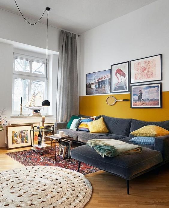 an eclectic living room with a color block accent wall, a grey sectional, layered rugs, a gallery wall and several coffee tables