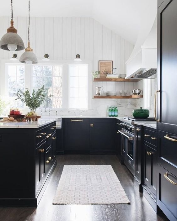 an elegant U-shaped kitchen with only lower black cabinets, white stone countertops and a white tile backsplash, metallic handles