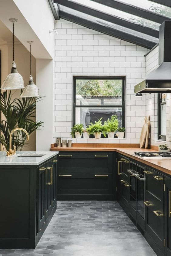 an elegant art deco kitchen in black, with butcherblock countertops, white subway tiles and a glazed ceiling