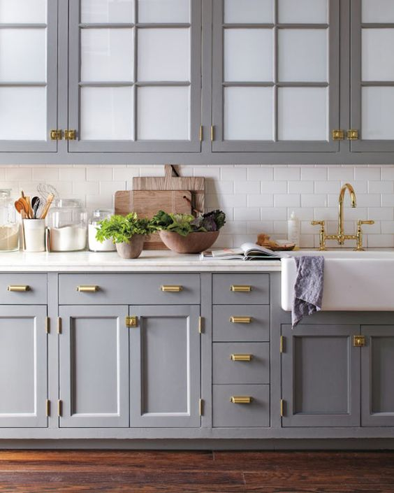 an elegant grey one wall kitchen with white tiles, gold handles and white stone countertops is a stylish space to cook here