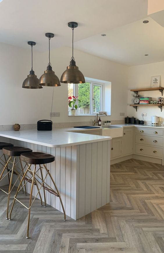 an elegant neutral kitchen with light grey cabinets, white stone countertops, dark brass touches and bold stools