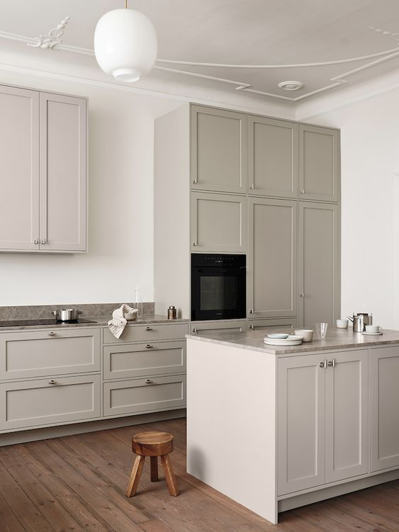 an ethereal Scandinavian kitchen with light grey vintage cabinetry, grey stone countertops, a cool kitchen island cabinet