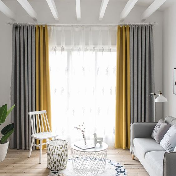 an ethereal living room in white and light grey, a light grey sofa, grey and yellow curtains, neutral furniture and beams