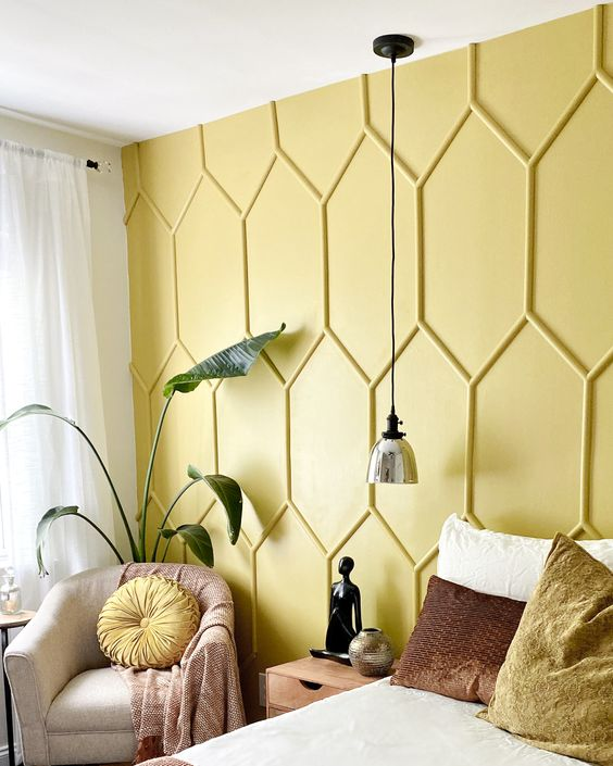 a bedroom with a yellow paneled accent wall and matching pillows to refresh the space for spring