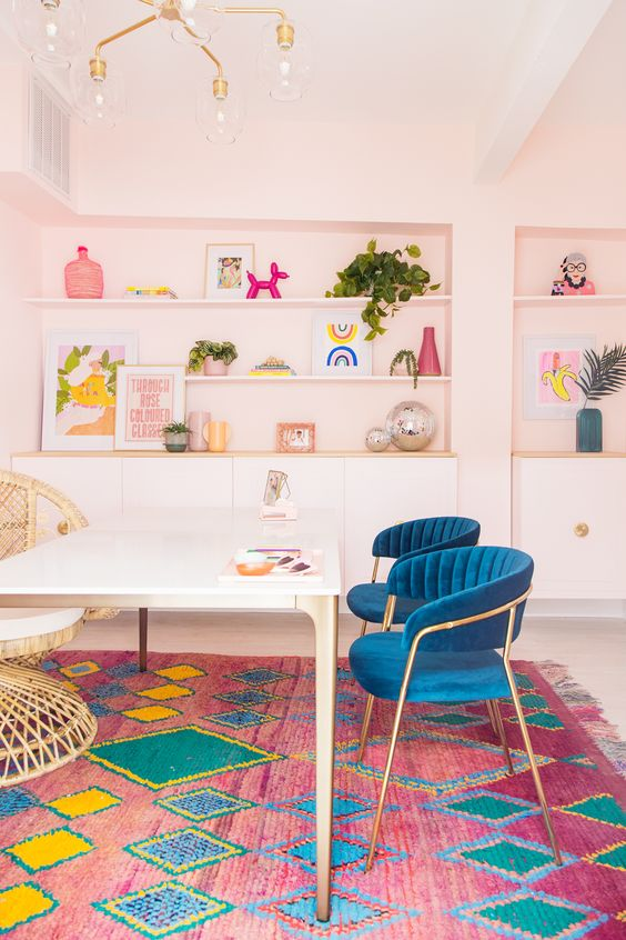 a bright home office with pastel pink walls, a colorful printed rug and navy chairs is a fun and bold spring-like idea