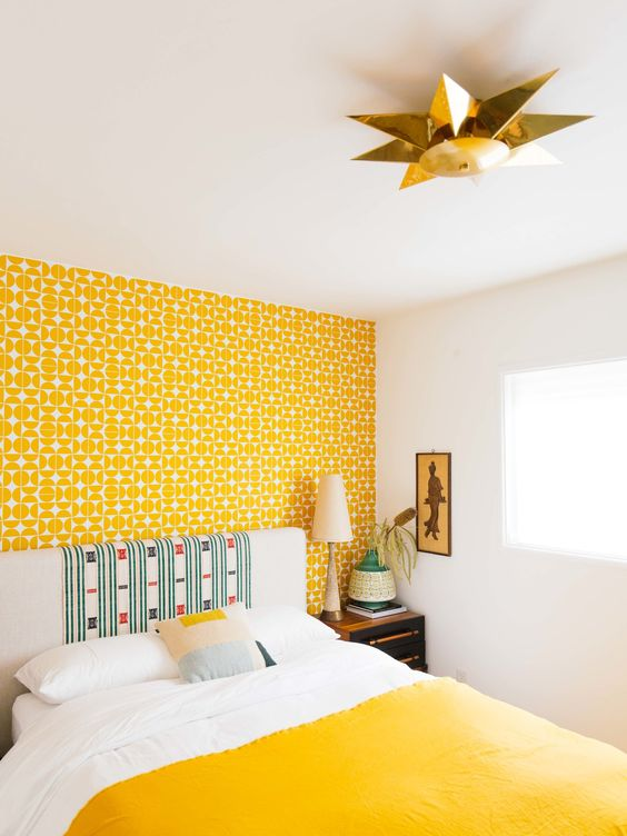 a bold yellow wallpaper accent wall and a matching bedspread will make your bedroom feel very spring like
