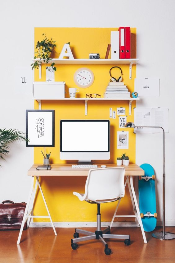a bright spring home office with a yellow accent wall, open shelves, a trestle desk and a white chair plus potted plants