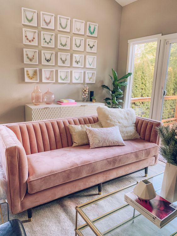 a neutral living room with grey walls, a pink sofa, neutral furniture, a table with gold frames and a cool gallery wall