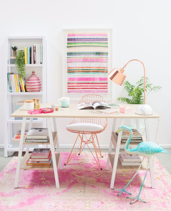 a pretty home office with a printed pink rug, a striped artwork, pink touches and a turquoise flamingo