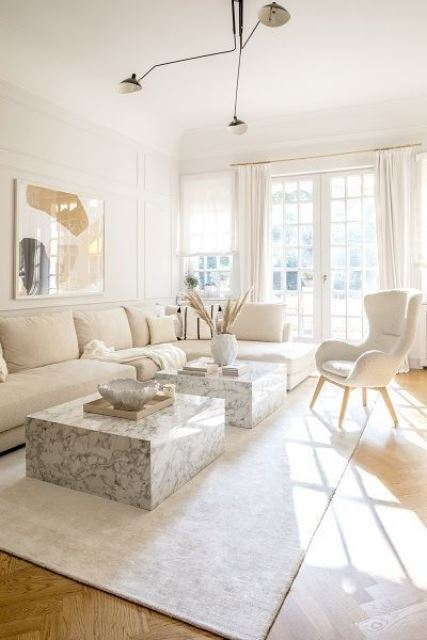 a refined neutral living room done in white and creamy tones, with chic marble slab tables and a statement artwork
