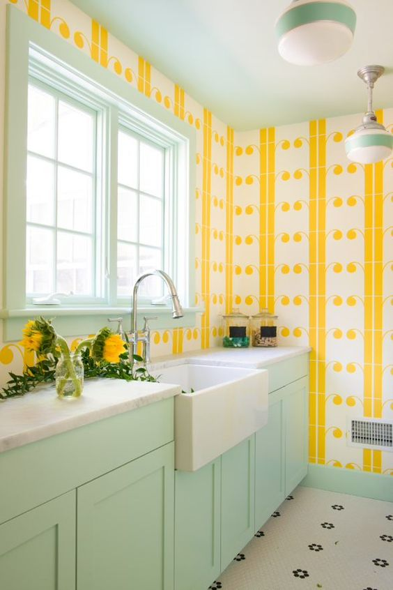 yellow and white printed wallpaper and mint cabinets and window frames make the kitchen bright, fun and very spring-like