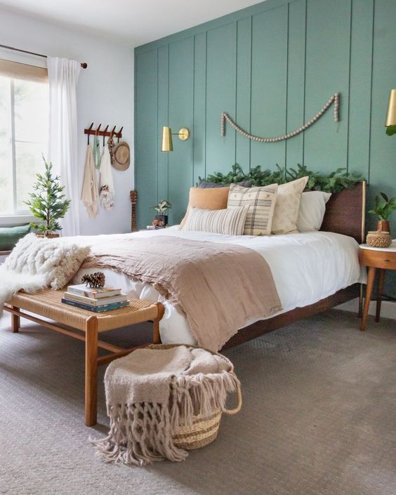 a farmhouse bedroom with a green accent wall, stylish modern furniture, printed bedding, a basket, some wall sconces and greenery