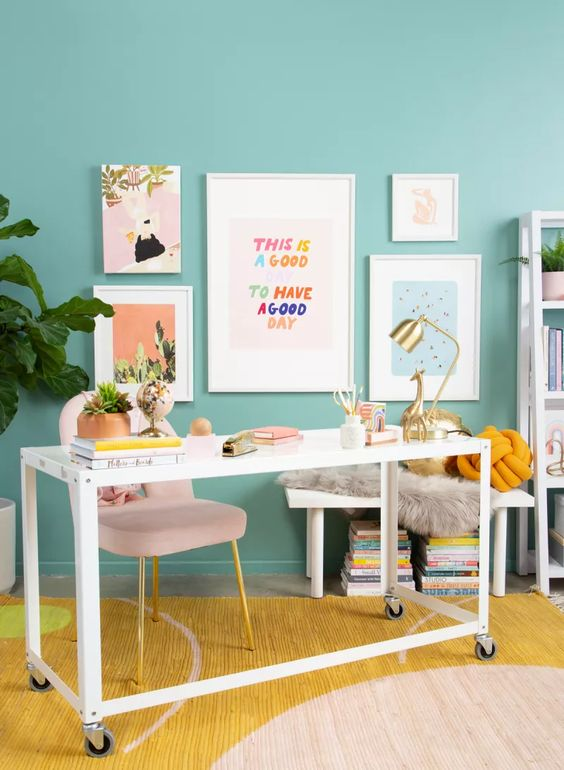 a fun and bright home office with a turquoise accent wall, white furniture, a colorful gallery wall and potted greenery