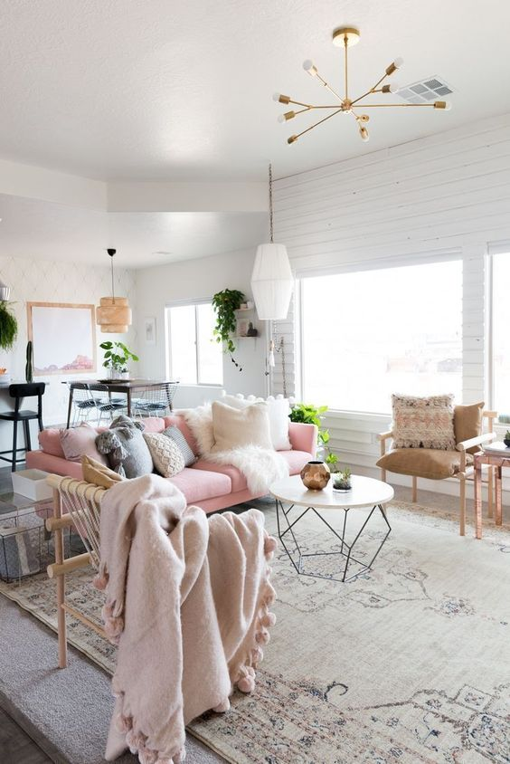 a neutral living room accented with pink touches, with a pink sofa, pastel pillows and blankets and potted greenery