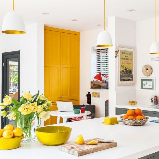 a spring kitchen accented with a sunny yellow pantry door, bold bowls and pendant lamps with gold