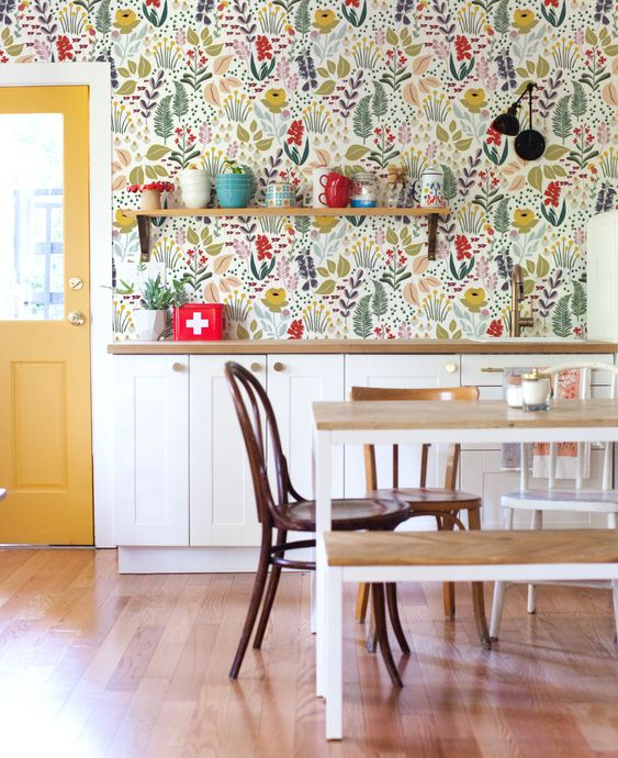 a retro kitchen in white done with pretty and bold floral wallpaper, with a table, a bench and some chairs is welcoming