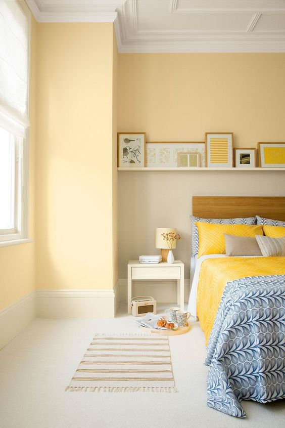 light yellow walls and bright yellow bedding infuse this space with color and make it look fun and bold