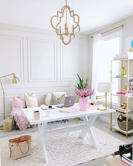 a chic neutral home office with a trestle desk, a sof and bright touches of pink that give a cute spring feel to the space