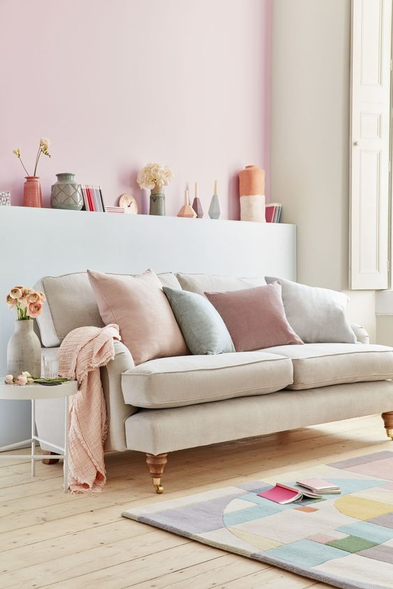 a pastel living room with neutral walls and a pink accent wall, refined furniture, pastel vases and pillows plus a color block rug