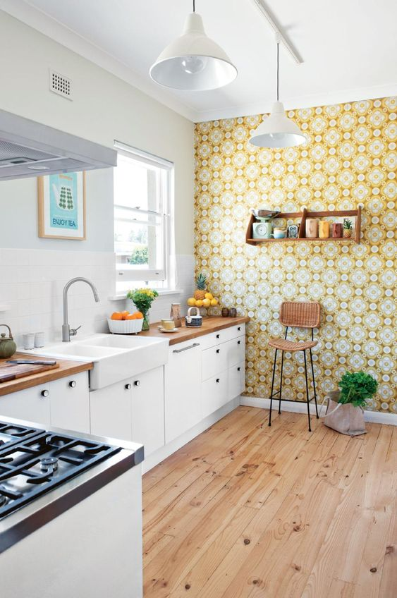 a pretty white kitchen accented with a bright yellow printed wallpaper to make the space feel spring-like