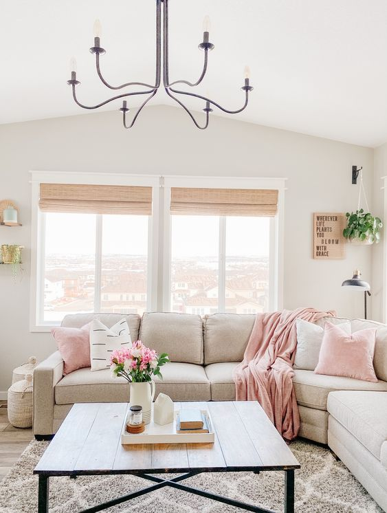 a neutral living room with pink touches, a vintage chandelier and pink blooms in a jug is a welcoming space