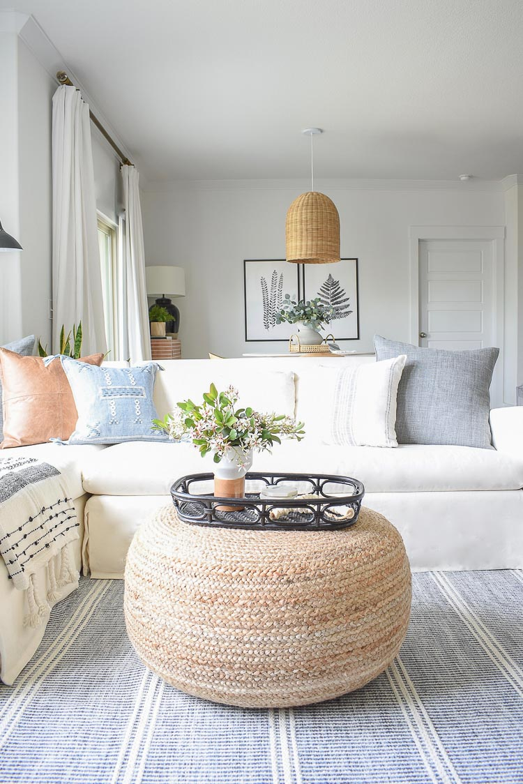 a fresh and welcoming spring living room in neutrals, with a sectional, pastel pillows, a rattan pendant lamp and an ottoman