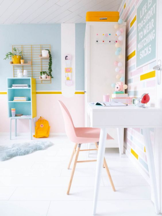 a lovely pastel home office in light blues, pink and yellow, with stripes and a light garland looks very spring-like and pretty