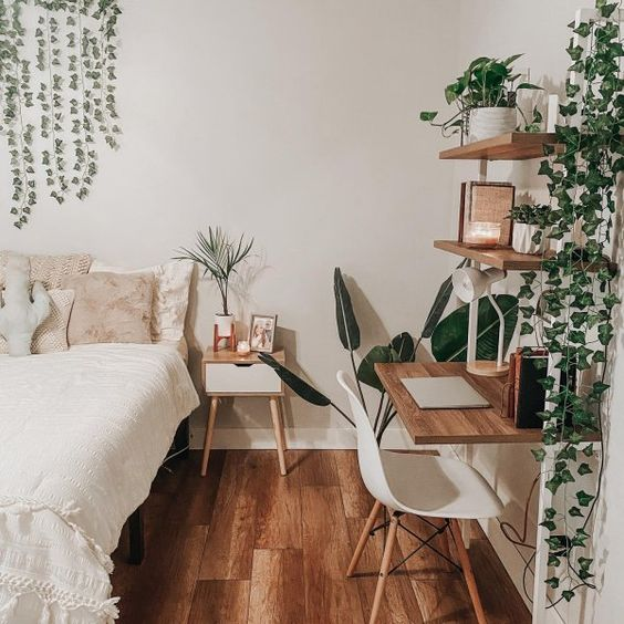 a stylish contemporary boho bedroom designed in neutrals, with potted greenery and plants that refresh the space