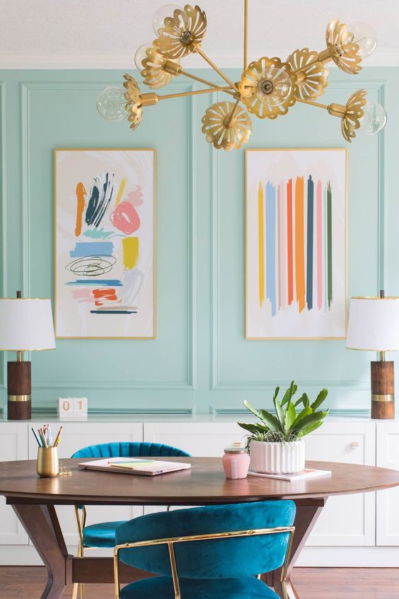 a mint home office with colorful artworks, teal chairs and a floral gold chandelier compose a lovely spring space to rock