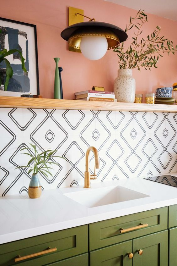 a pink half wall, printed panels, green cabinetry and brass handles make up a very cool kitchen setup