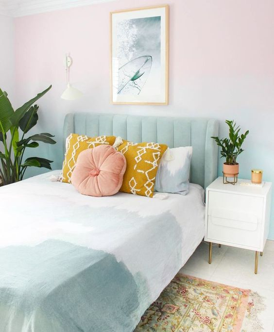 a spring bedroom with an ombre pastel wall, a pale green bed, green tie-dye bedding and mustard pillows