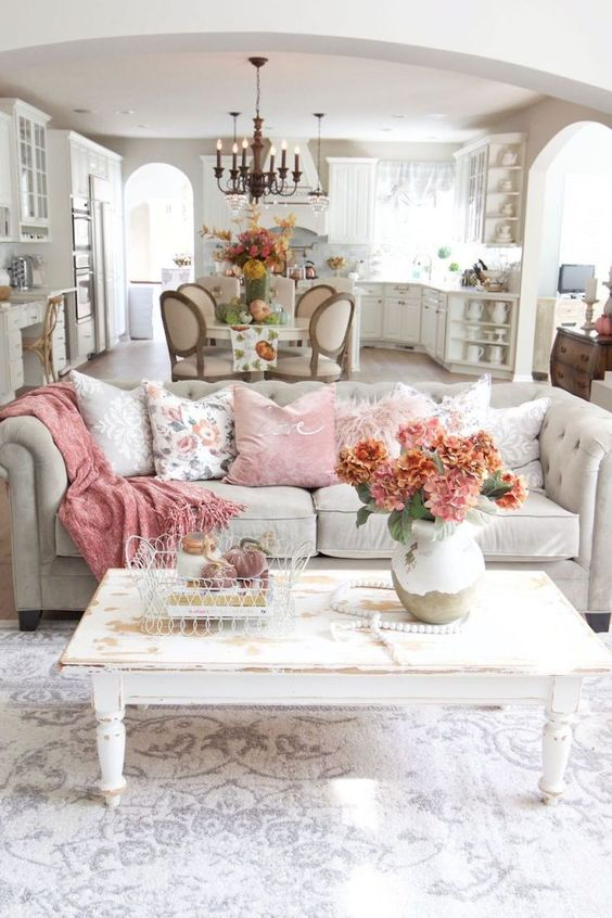 a neutral and pastel living room with a grey sofa, floral and pastel pillows, a pink blanket and a shabby chic table