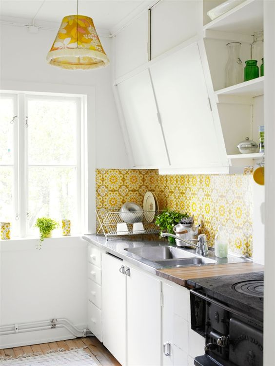yellow printed tiles and a matching pendant lamp spruce up the neutral kitchen decor and bring much color to the space