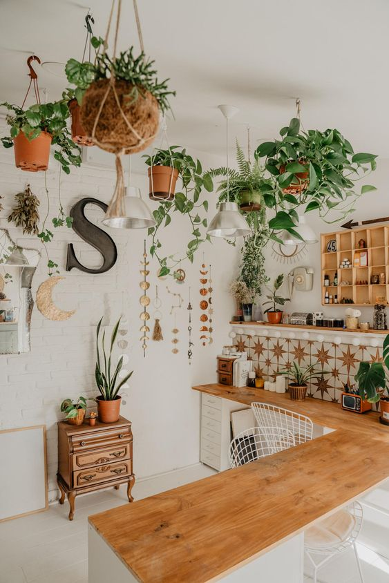 a boho kitchen with a whole number of potted greenery, vines and other plants over the space looks amazing