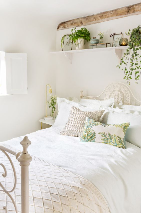 a neutral bedroom spruced up with potted greenery for spring, with printed pillows and candles is very cozy
