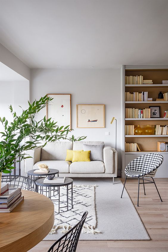 an airy spring living room done in light greys, comfy modern furniture, a gallery wall and some green branches in a vase