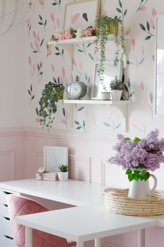 a lovely spring home office with a floral wallpaper wall, shelves, pink paneling, a pink chair, potted greenery and lilac in a jug