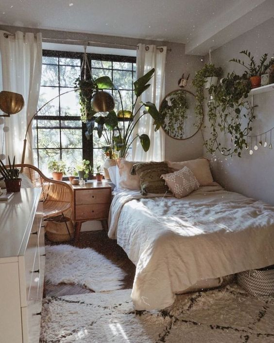 a neutral bedroom in boho style looks rather cozy and welcoming, and spring-ready thanks to lots of potted greenery