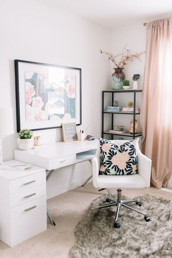 a pretty home office in neutrals accented with blush curtains, a floral artwork and a floral pillow is a very welcoming