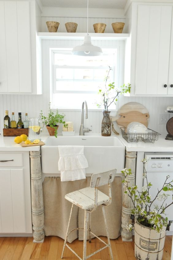 potted greenery and blooming branches in vases bring a fresh spring feel to this shabby chic kitchen
