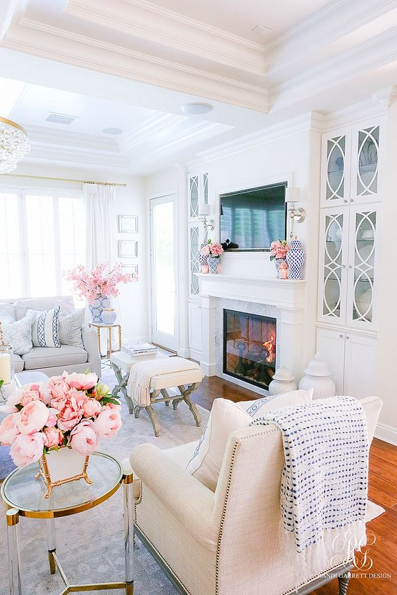 a neutral living room with chic and comfy furniture, lots of pink blooms and some printed blue textiles