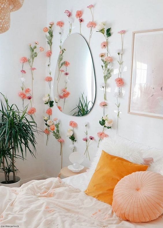 fake blooms attached around the mirror and pink and orange bedding will bring color and romance to the bedroom