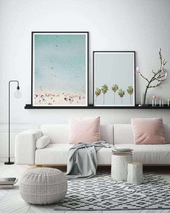 a welcoming and fresh living room in neutrals with some prints, a gallery wall with beach-inspired prints is amazing