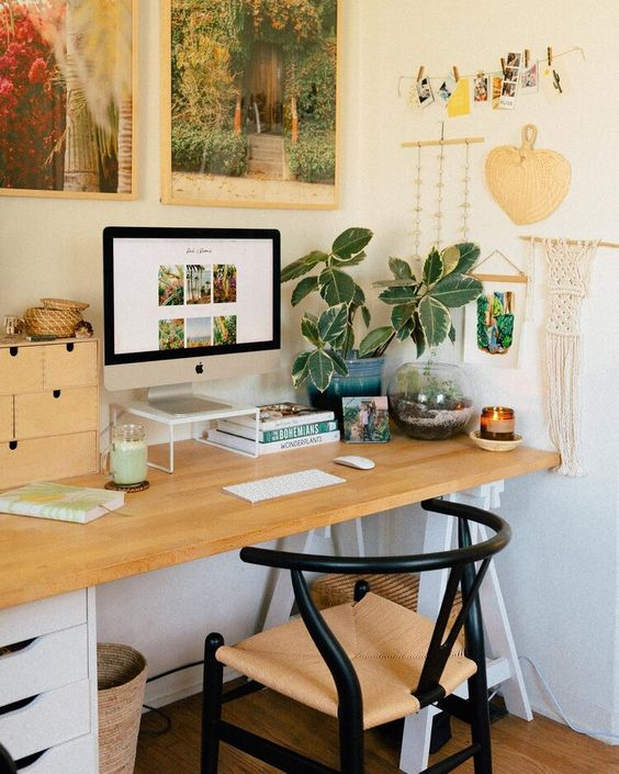 a boho home office with a comfy desk, a woven chair, potted greenery, a macrame hanging and bright artworks in frames